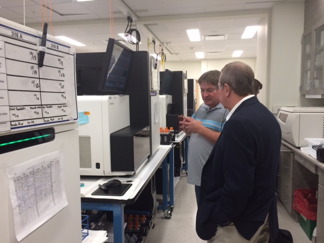 A technician shows Bob some of the equipment used in SCAD genetic research.